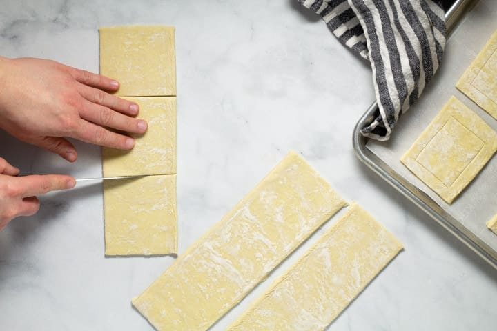White marble counter top with a sheet of puff pastry being cut into 3 squares