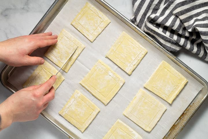 Puff pastry squares on a parchment lined baking sheet with a knife scoring the crust of each square