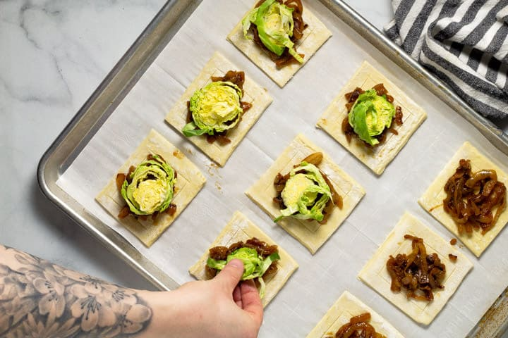Brussels sprouts being added to puff pastry squares on a baking sheet