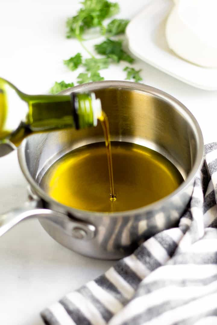 Silver sauce pan with olive oil being poured into it