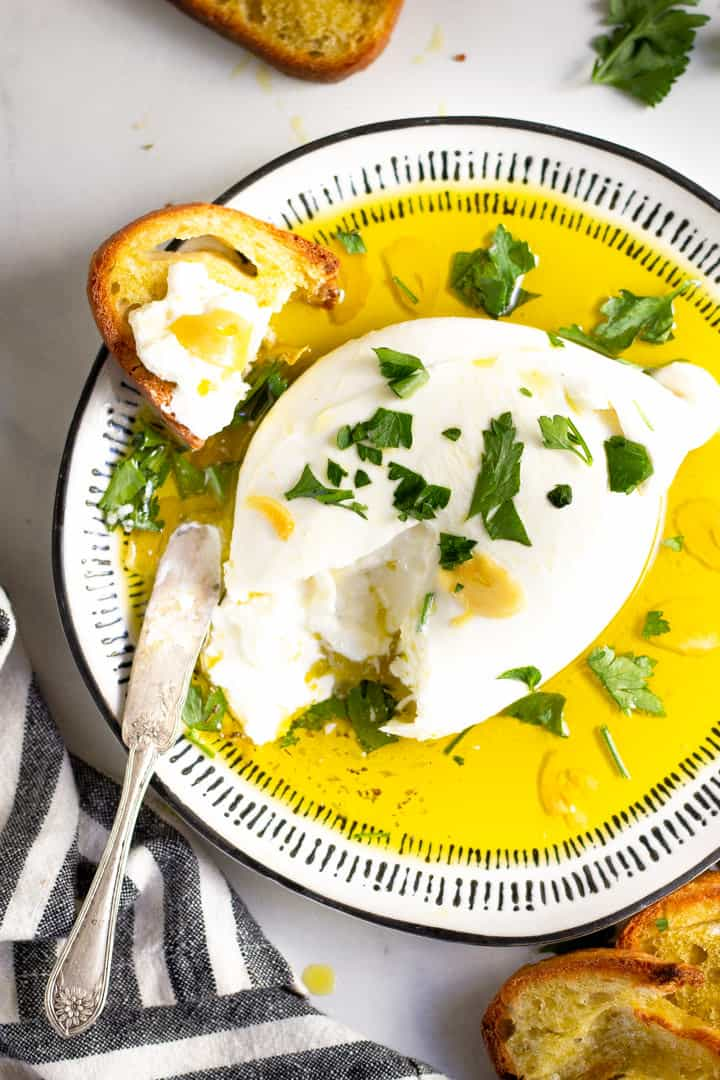 Black and white plate with burrata appetizer garnished with fresh parsley