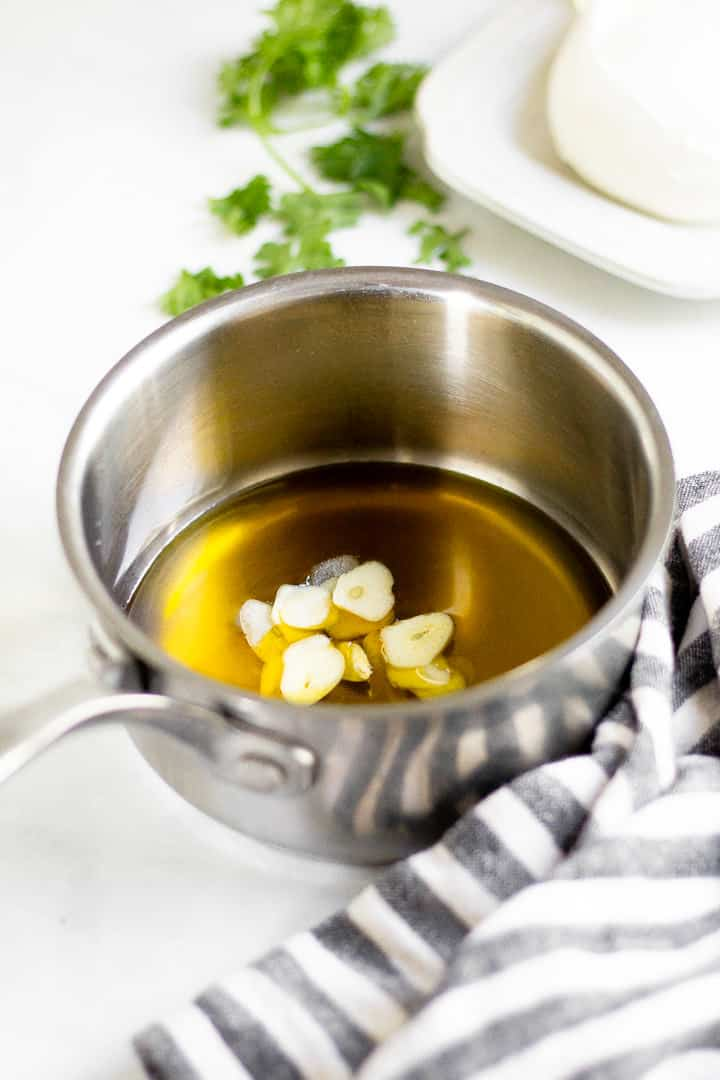 Metal saucepan with olive oil and sliced garlic