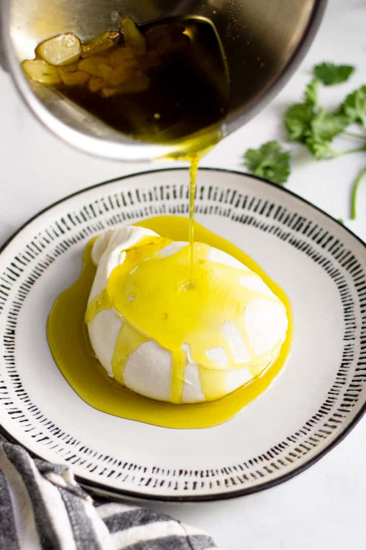 Burrata on a white plate with olive oil being poured over it