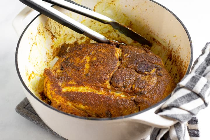 Large white pot filled with seared pork roast rubbed with curry spices