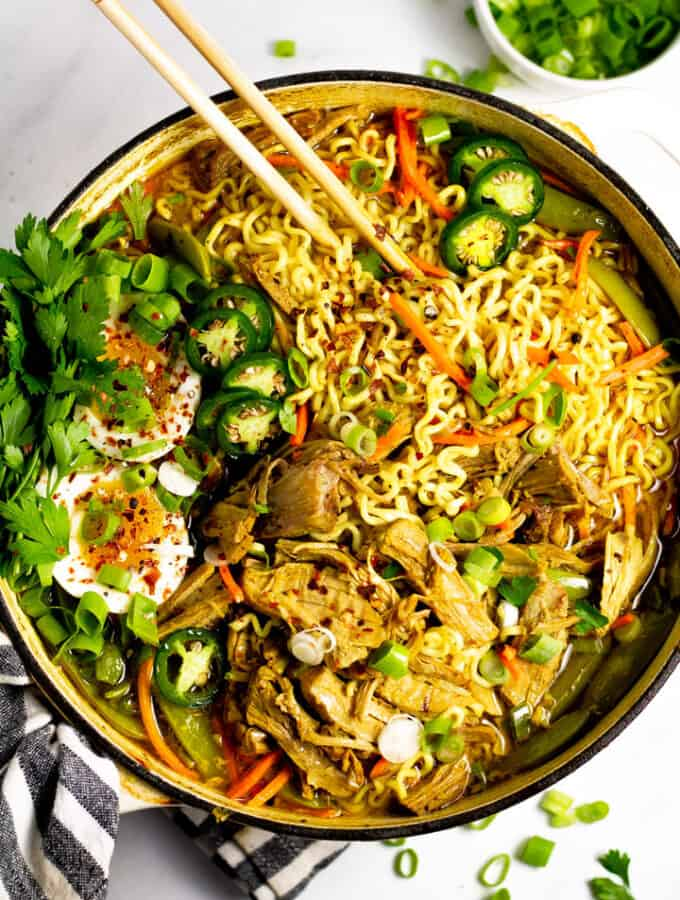 Overhead shot of a large pot filled with curry pork ramen garnished with fresh parsley and sliced jalapenos