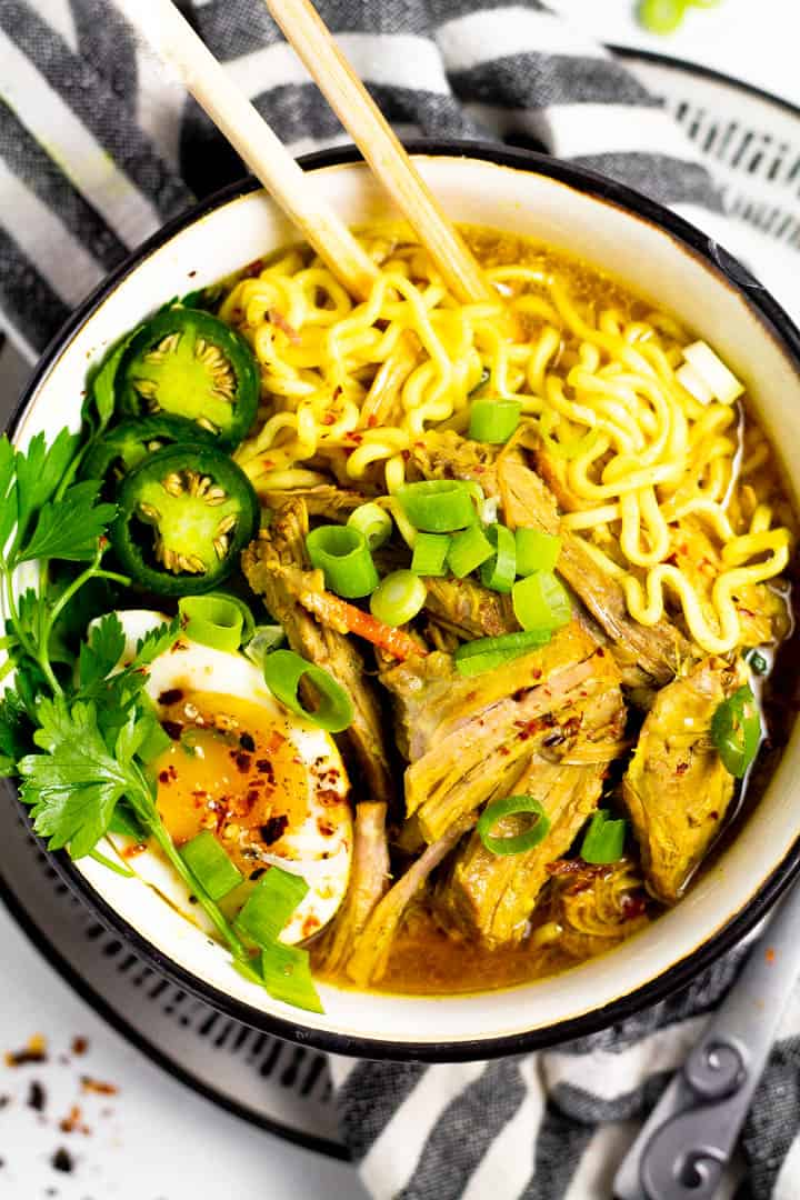 Overhead shot of a large bowl filled with curry pork ramen garnished with fresh parsley and sliced jalapenos