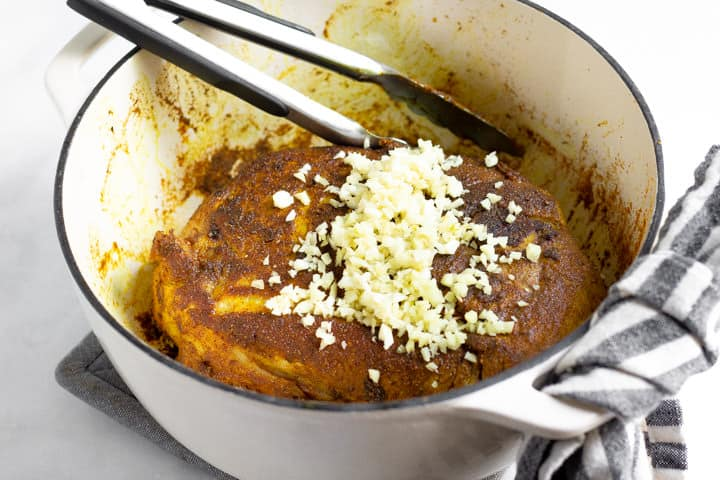 Large white pot filled with seared pork roast rubbed with curry spices and garlic