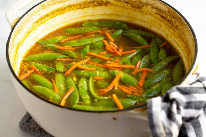 Large pot filled with peas and carrots in a curry broth