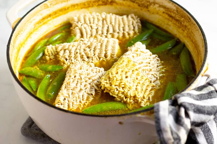 Ramen noodles being added to veggies and curried broth