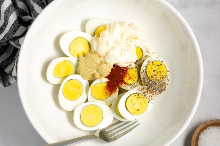 Large white bowl filled with ingredients to make deviled egg salad
