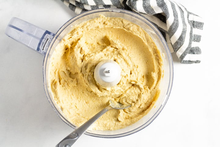 Food processor filled with ingredients to make homemade hummus