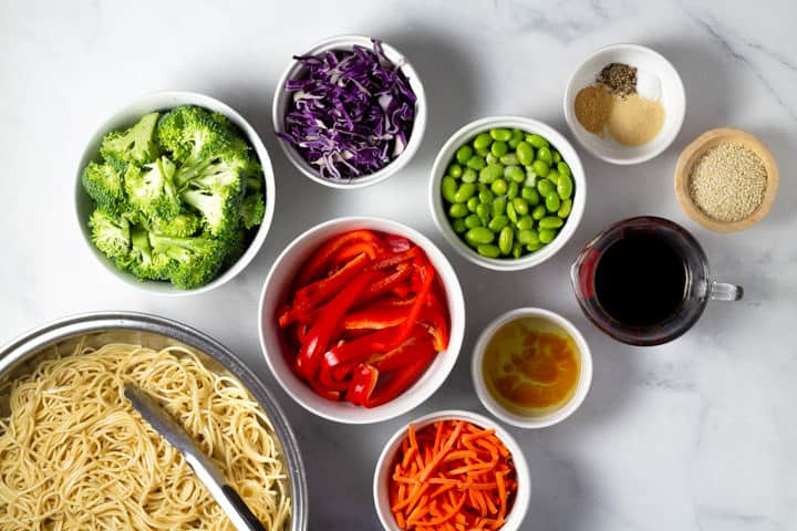 White marble counter top covered with the ingredients to make veggie lo mein