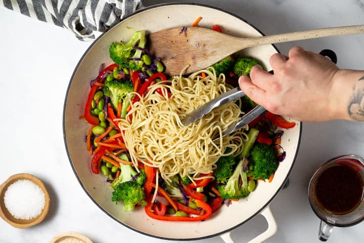 Overhead shot of noodles being added to a pan of veggie lo mein