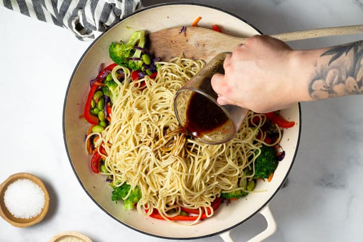 Overhead shot of stir fry sauce being added to a pan of veggie lo mein
