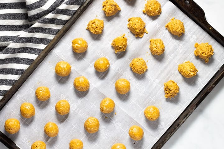 Parchment lined baking sheet with peanut butter balls on it