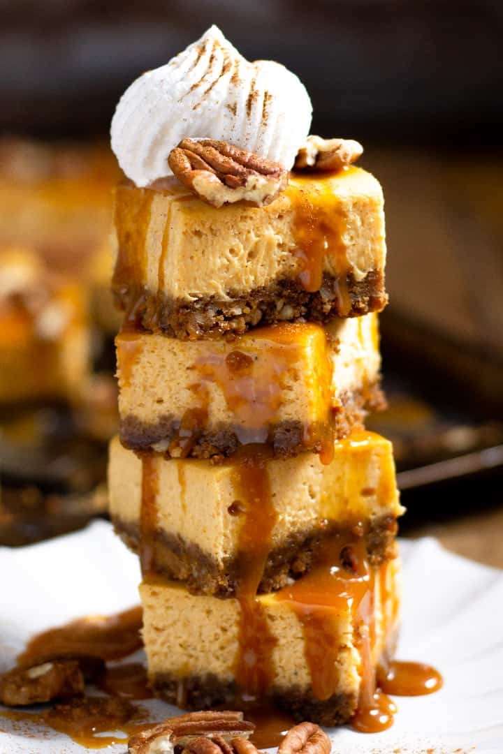 Tower of pumpkin cheesecake bars garnished with caramel and pecans