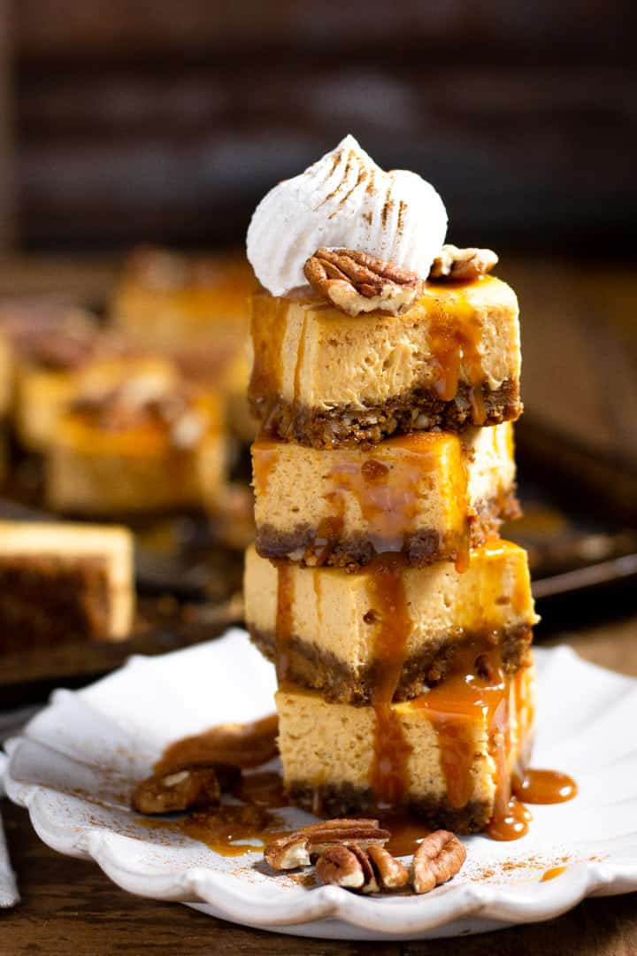 Tower of pumpkin cheesecake bars garnished with caramel and whipped cream