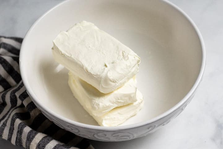 Large white bowl with three packages of cream cheese in it