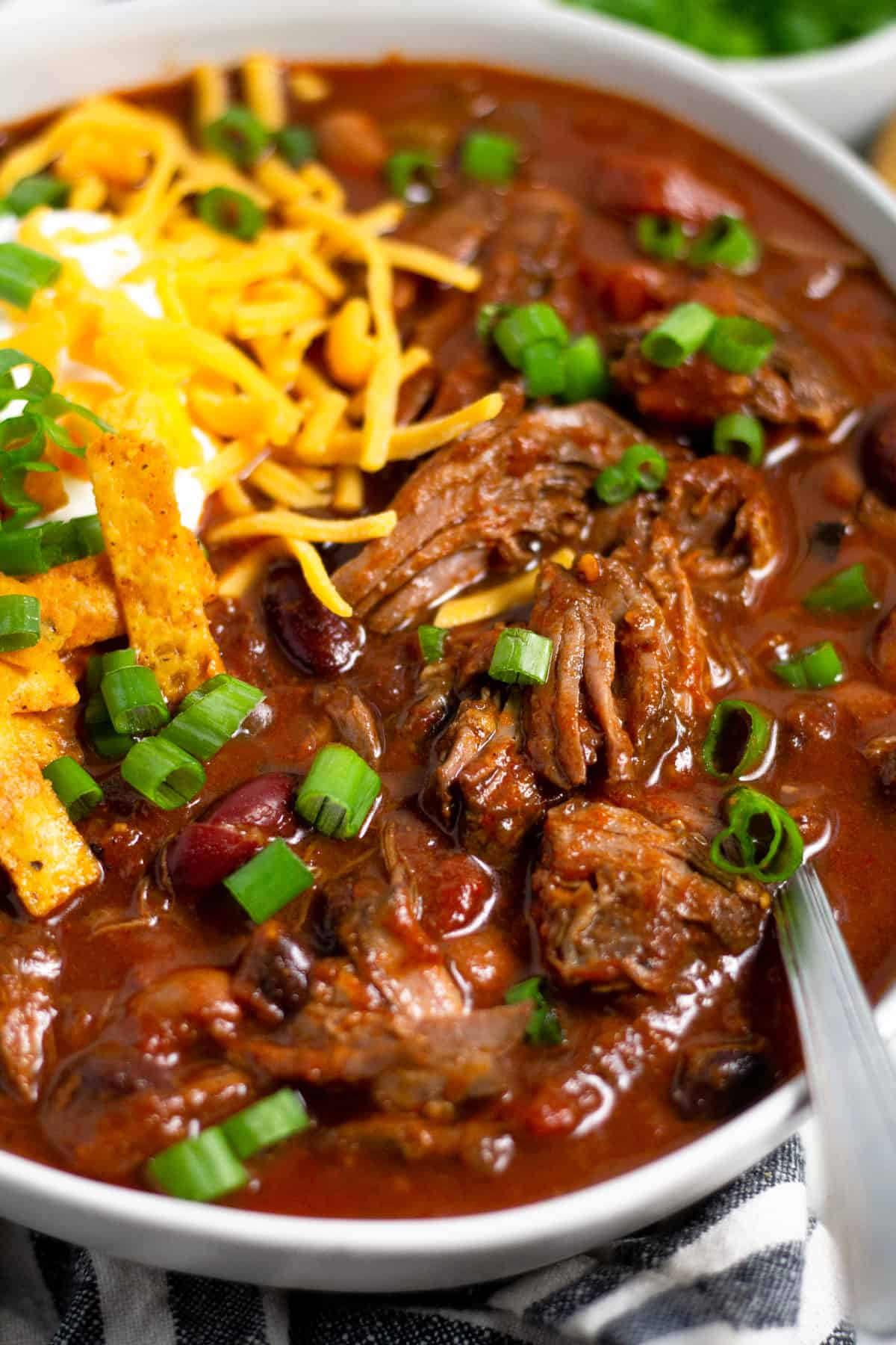 Close up shot of a bowl of short rib beef chili topped with sour cream and cheese