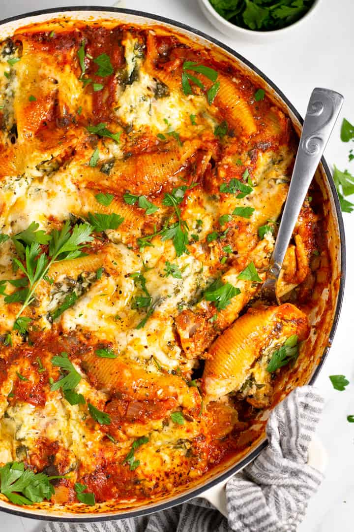 Overhead shot of a large white pan filled with stuffed shells garnished with fresh parsley