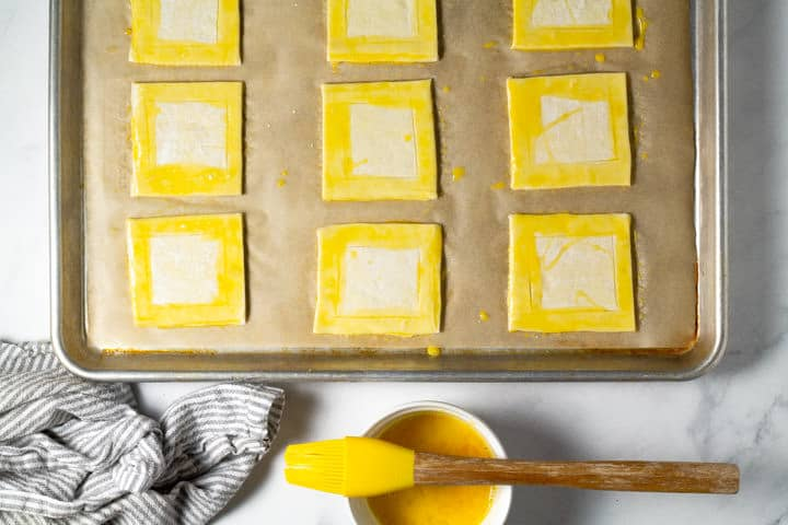 Parchment lined baking sheet with squares of puff pastry brushed with egg wash