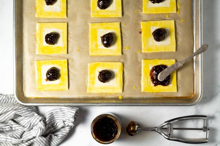 Parchment lined baking sheet with squares of puff pastry on it with fig jam being added