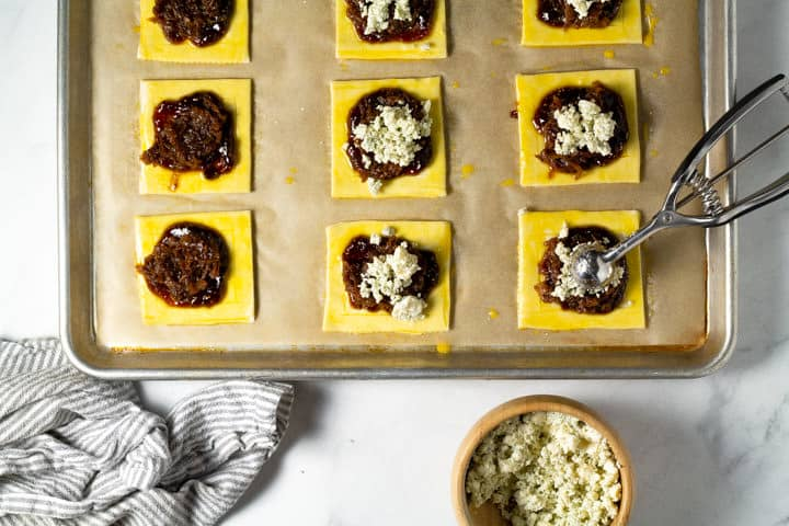 Parchment lined baking sheet with squares of puff pastry on it being topped with blue cheese