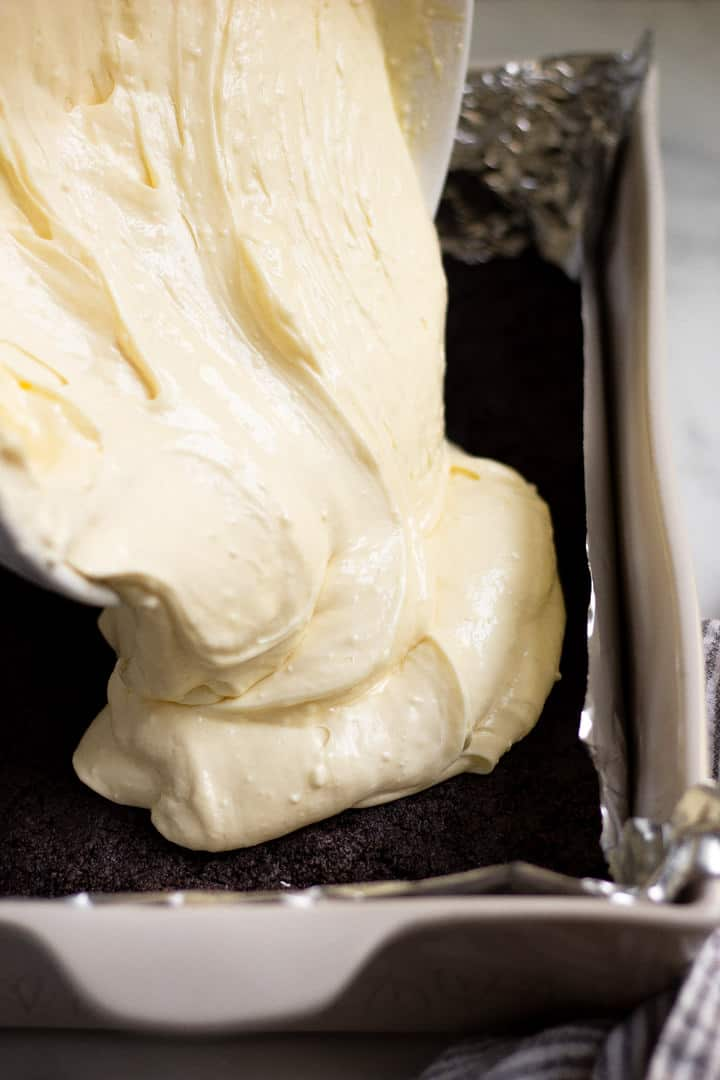 Cheesecake batter being poured onto an oreo crust