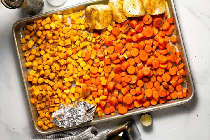 Baking sheet filled with veggies seasoned with spices
