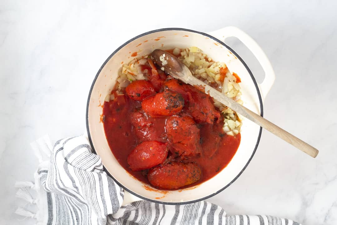 Large white pot filled with tomatoes onions and garlic for tomato soup