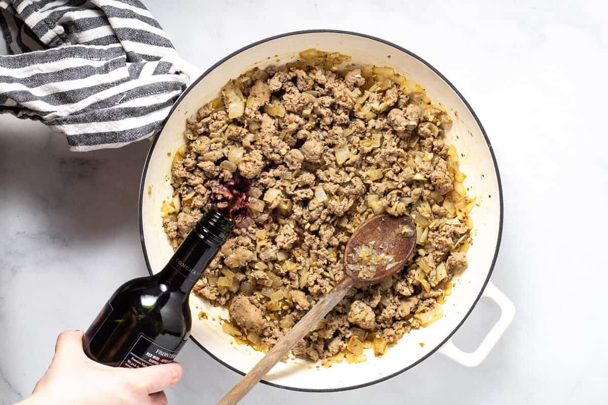 Large white saute pan filled with browned sausage with red wine being poured in