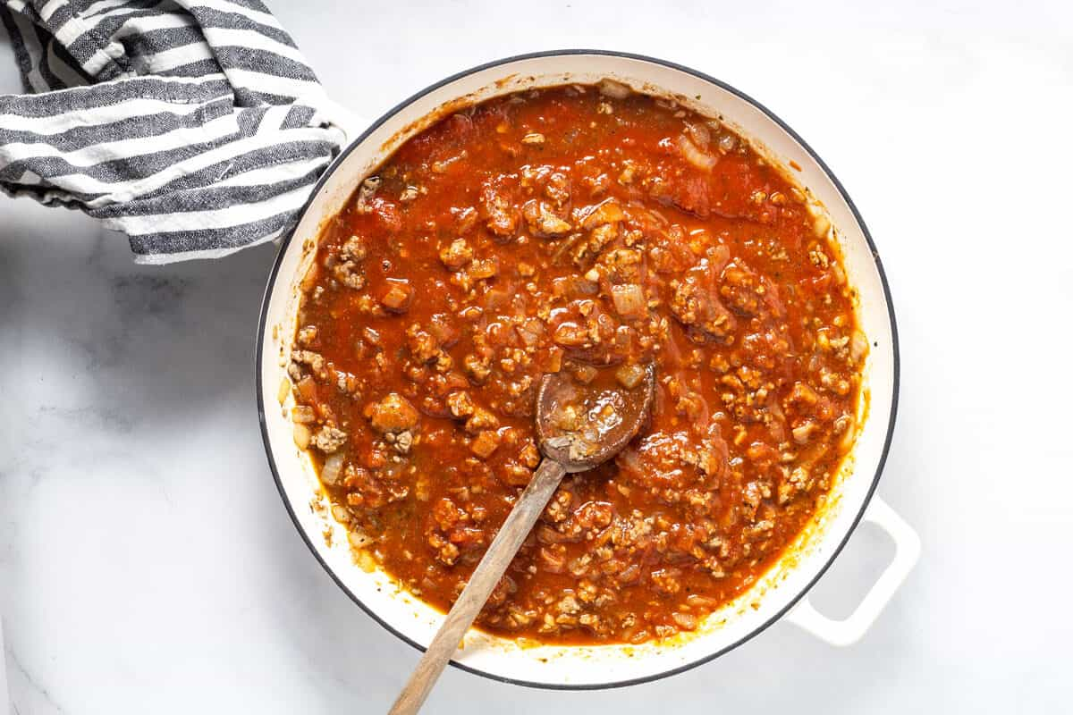 Large white saute pan filled with spaghetti sauce and ground sausage