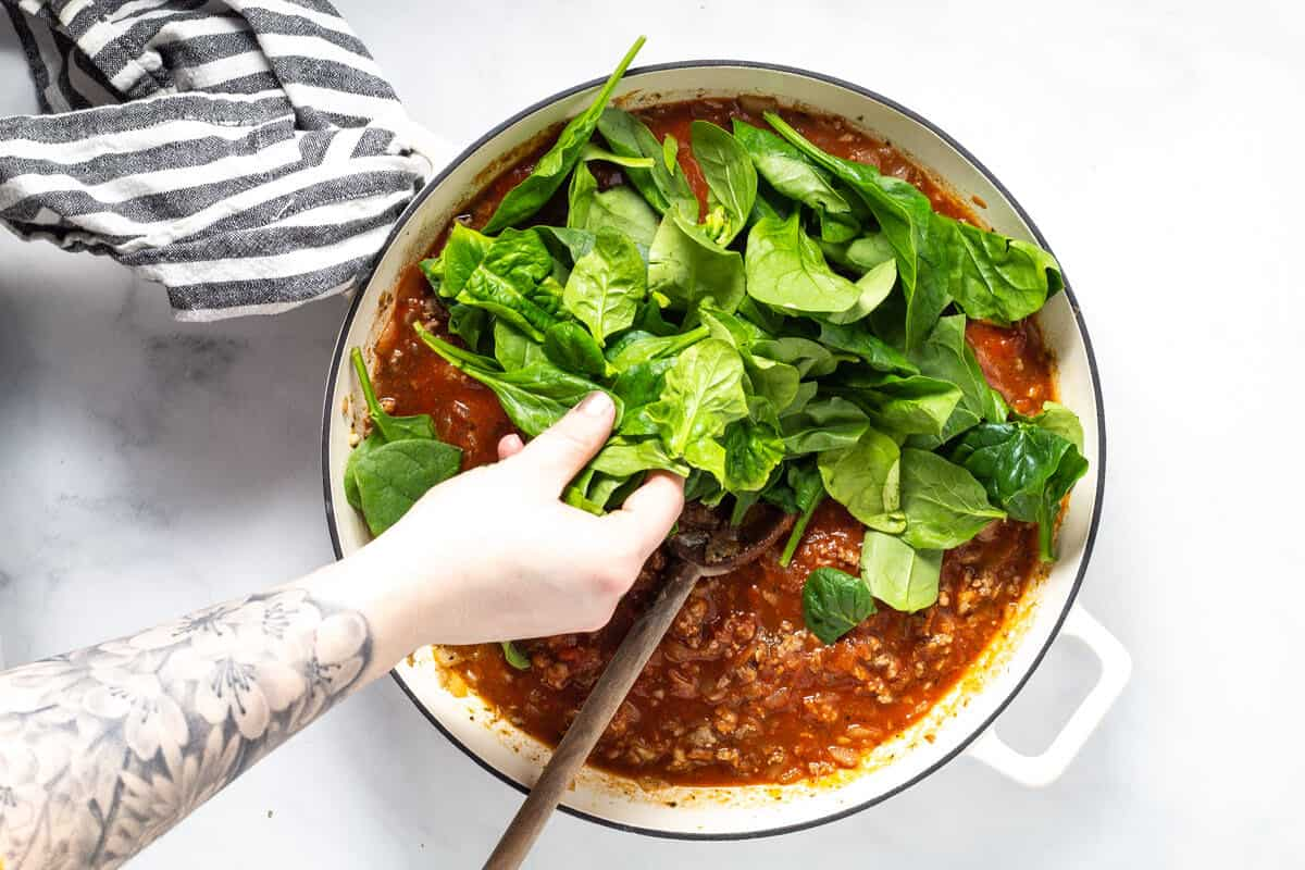 Large white saute pan filled with spaghetti sauce with fresh spinach being added to it