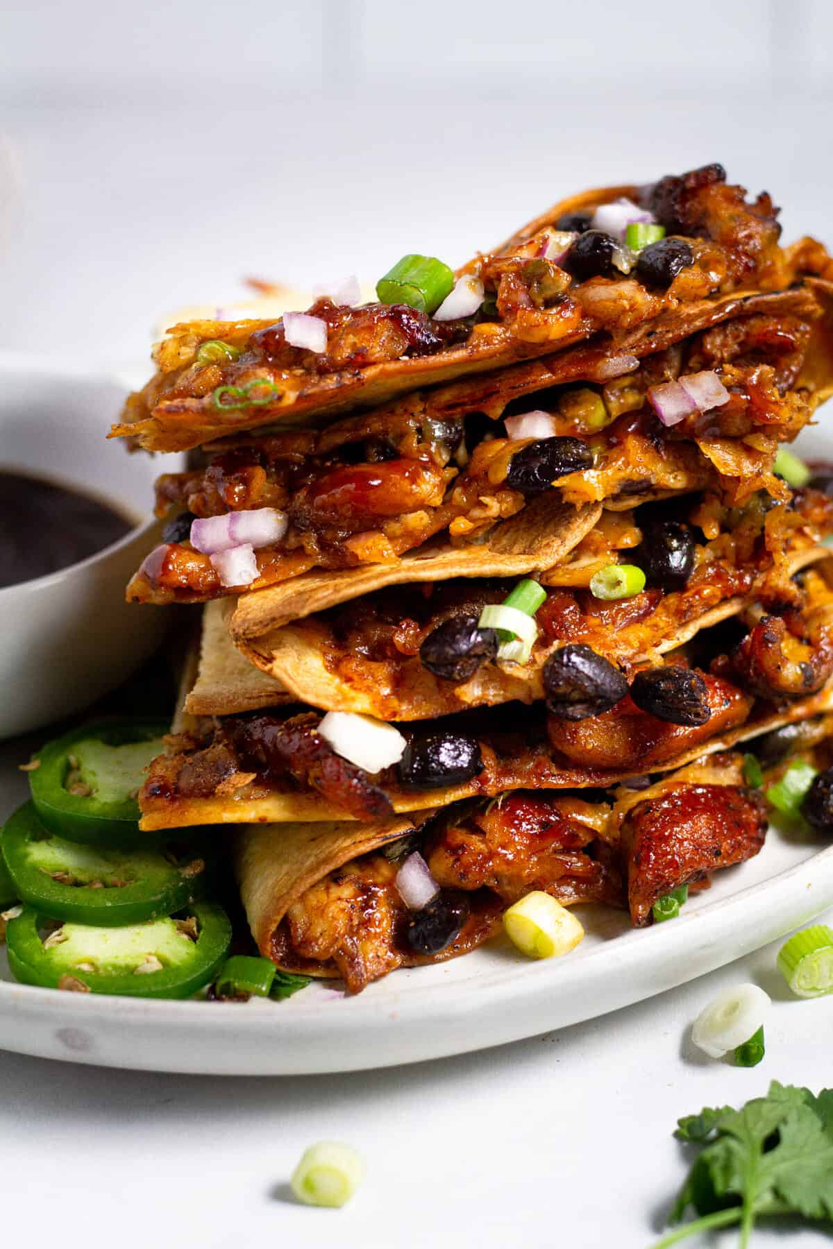 Barbecue chicken quesadillas sliced and stacked on a large white plate