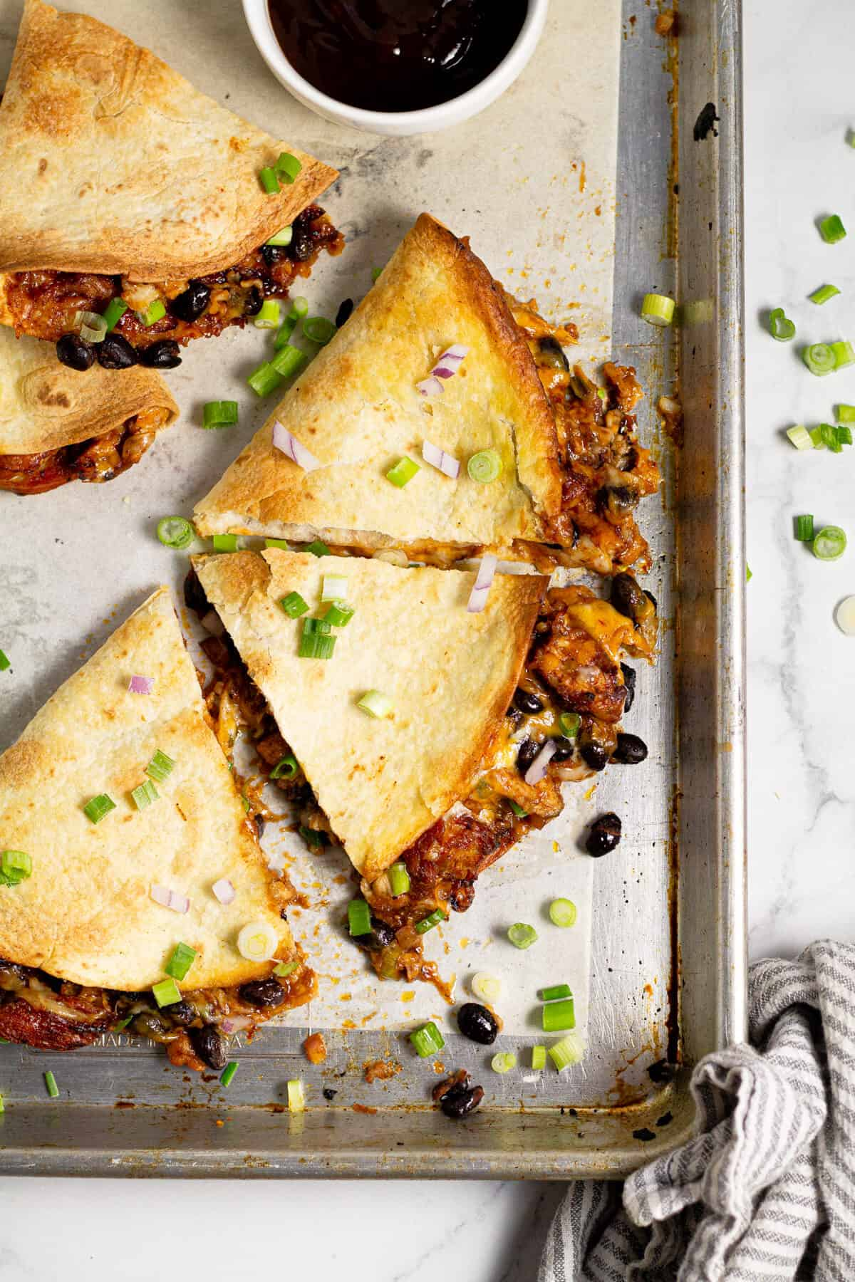 Overhead shot of a sheet pan of barbecue chicken quesadillas garnished with green onion