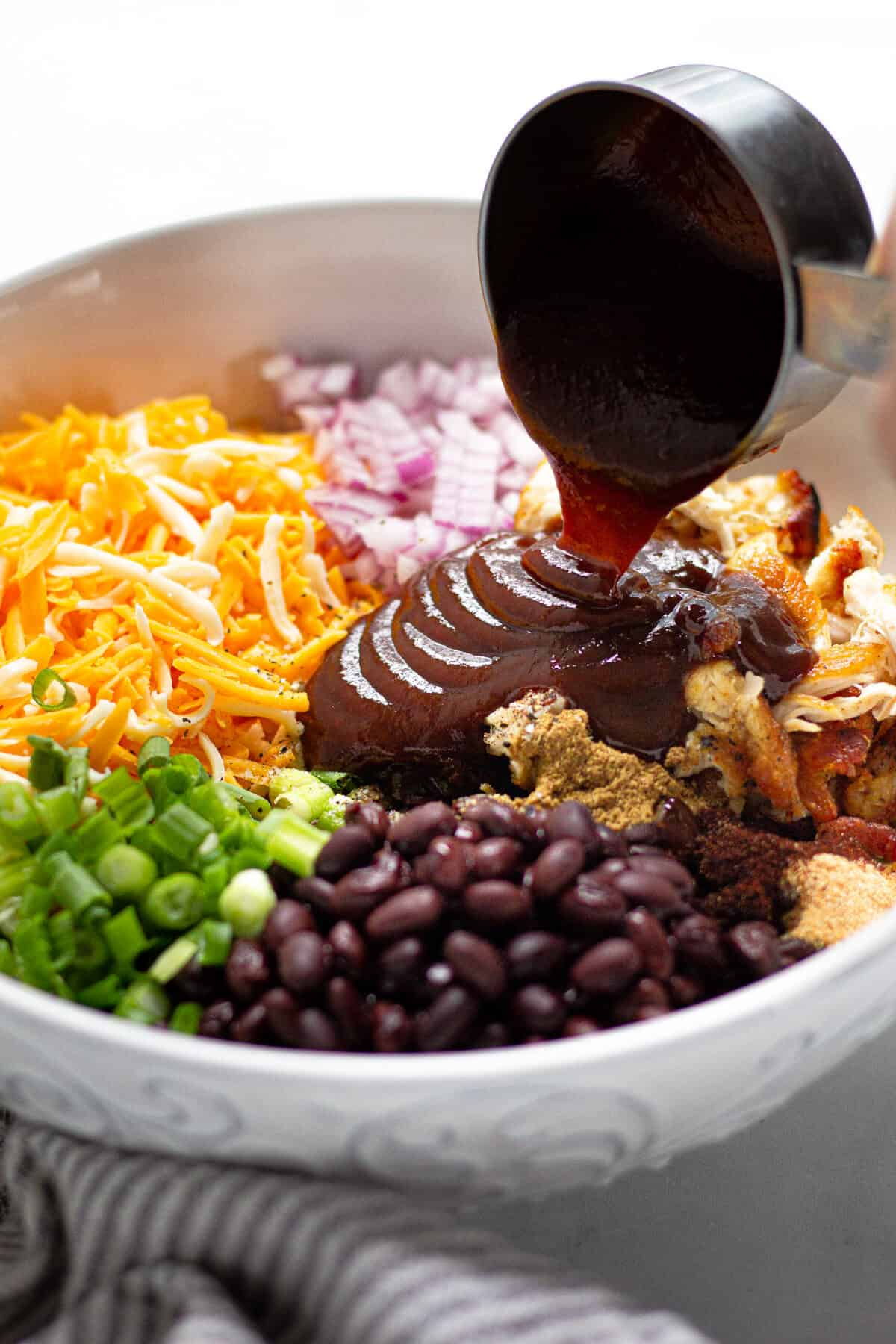 BBQ sauce being poured into a bowl filled with ingredients to make barbecue chicken quesadillas