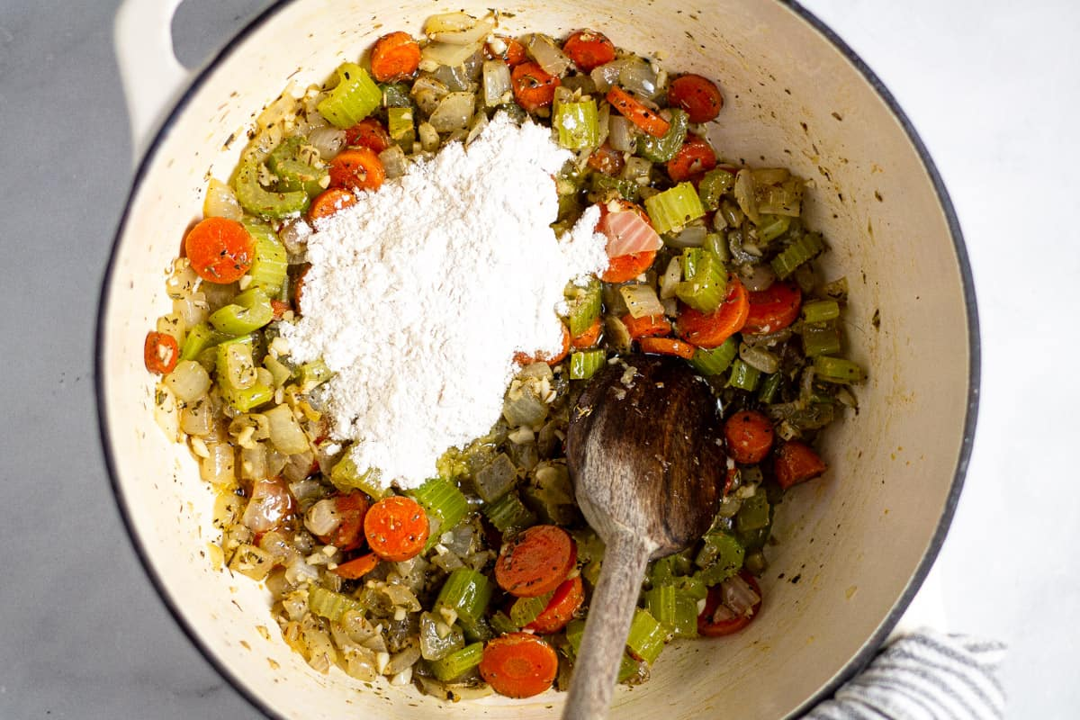 White dutch oven with cooked veggies and flour in it