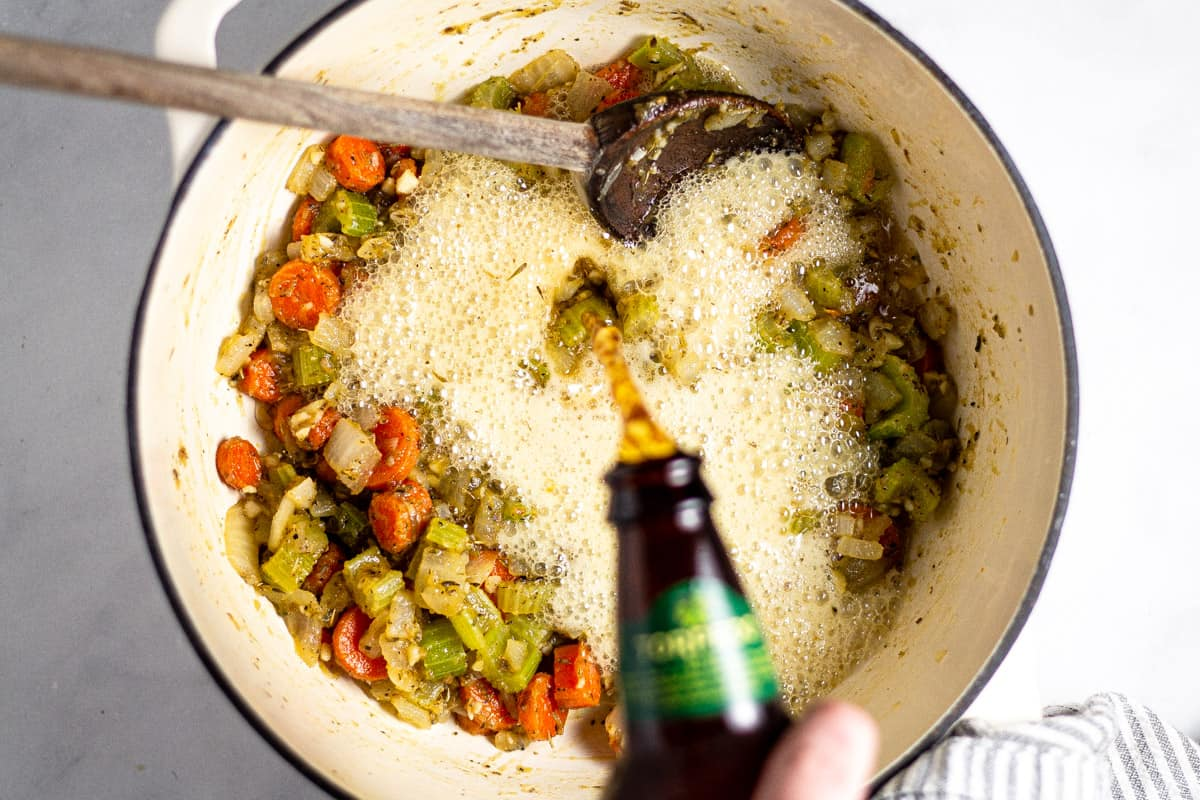 White dutch oven with cooked veggies and beer being poured into it