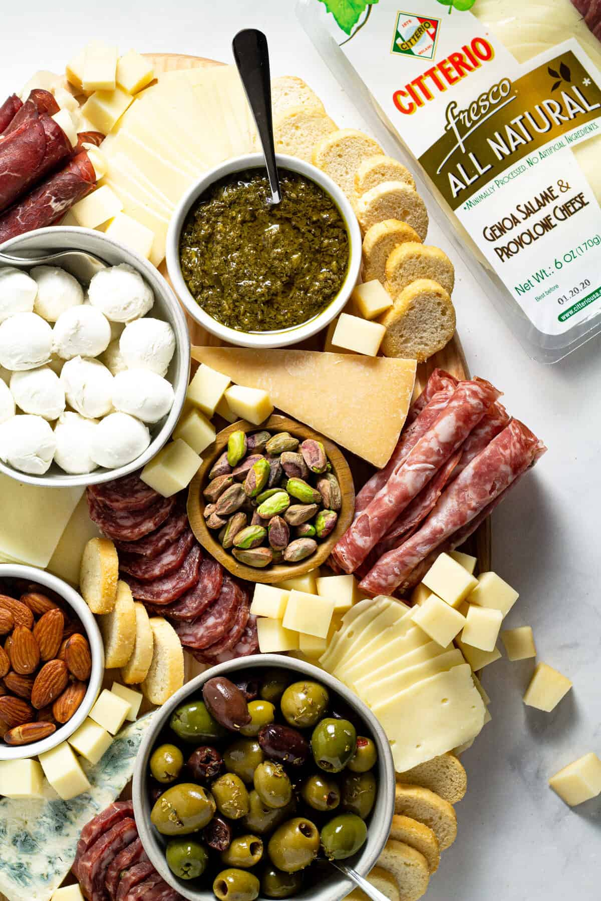 Overhead shot of a cheese board filled with a variety of meats cheeses and nuts