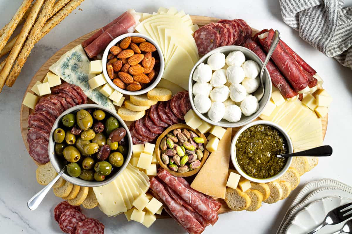 Overhead shot of a cutting board filled with meat and cheese creating a cheese board
