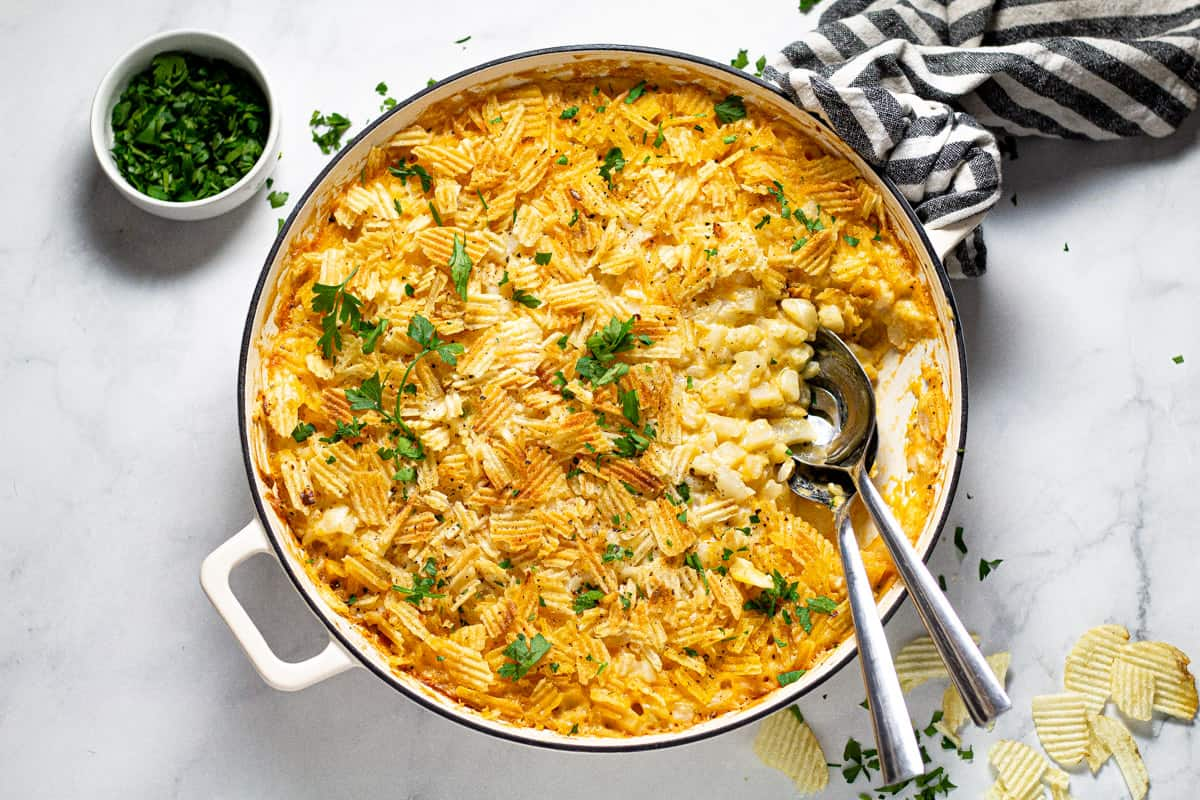 Overhead shot of a large pan filled with cheesy potato casserole garnished with fresh parsley