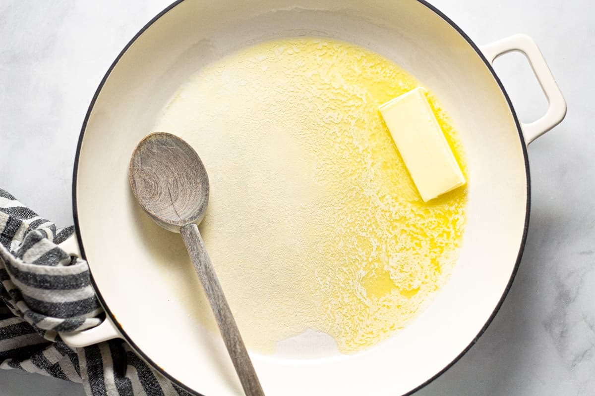 Large white pan filled with a stick of melting butter