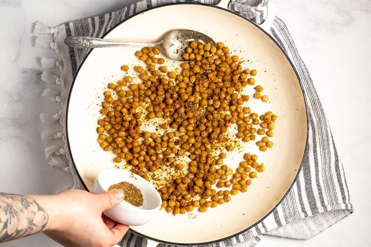 Large white saute pan with crispy seasoned chickpeas in it