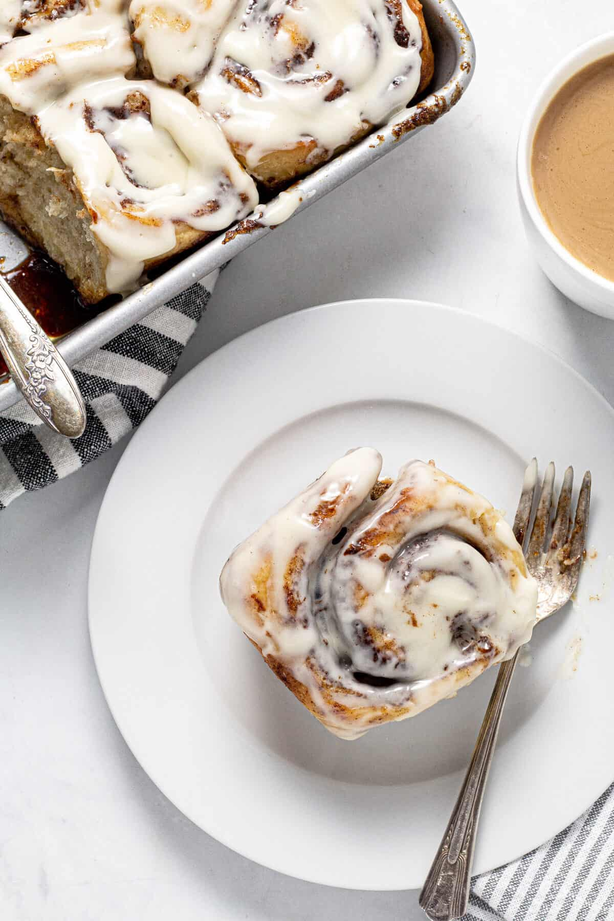 Overhead shot of a table with a pan of cinnamon rolls and a cup of coffee