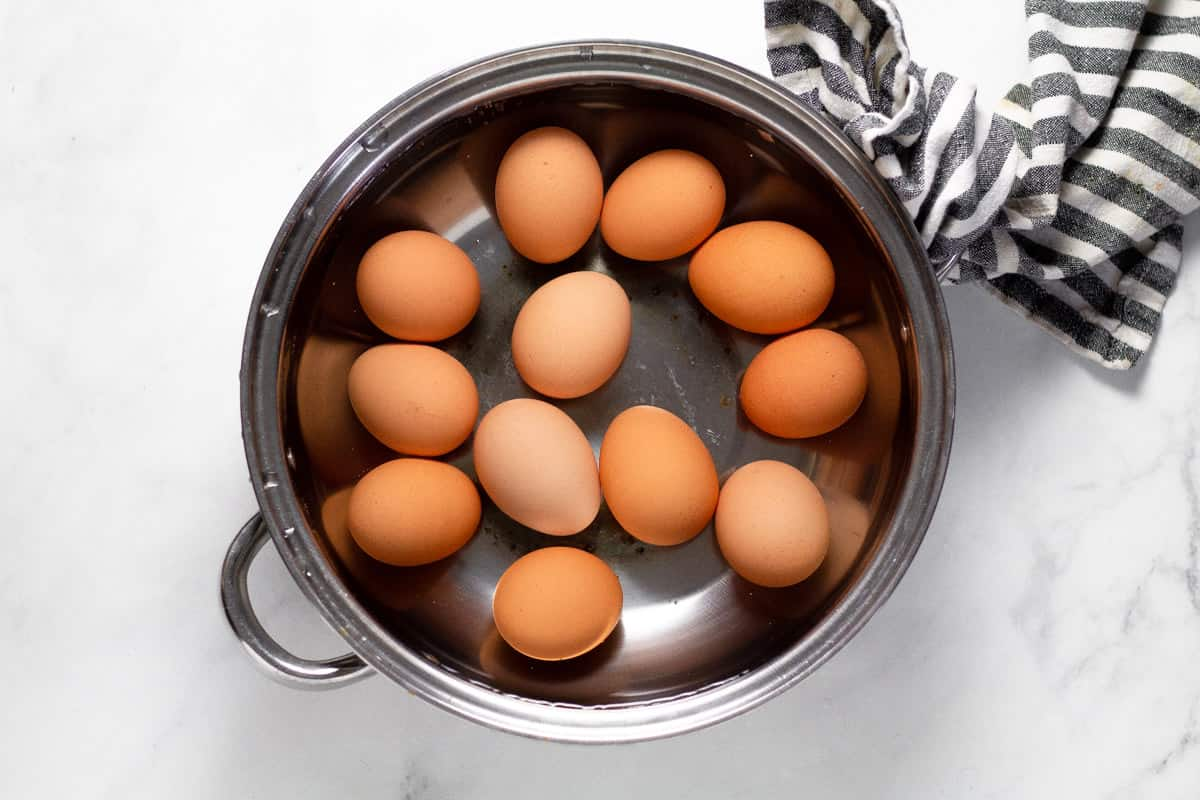 Large metal pot filled with water and hard boiled eggs on a white counter top