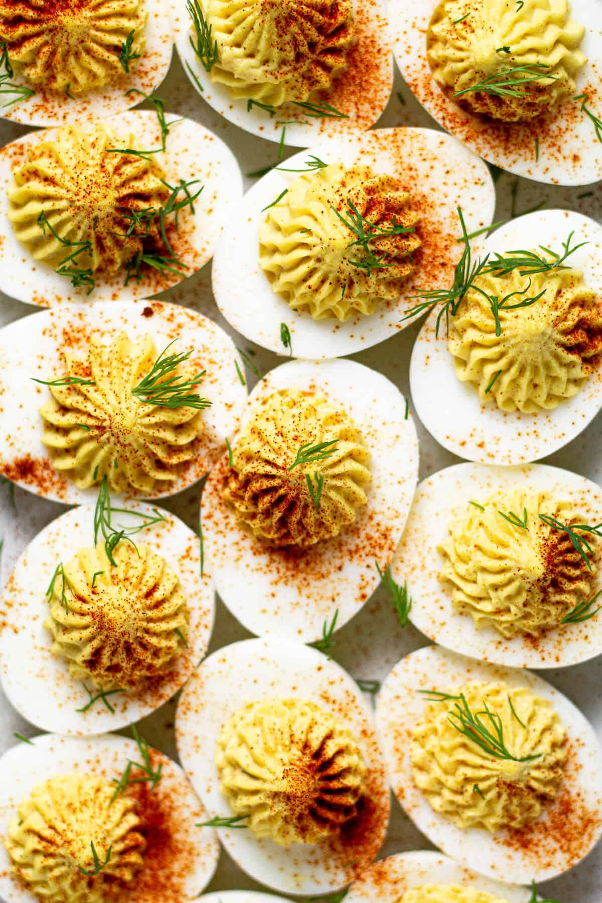 Overhead shot of several curry deviled eggs on a white marble counter top