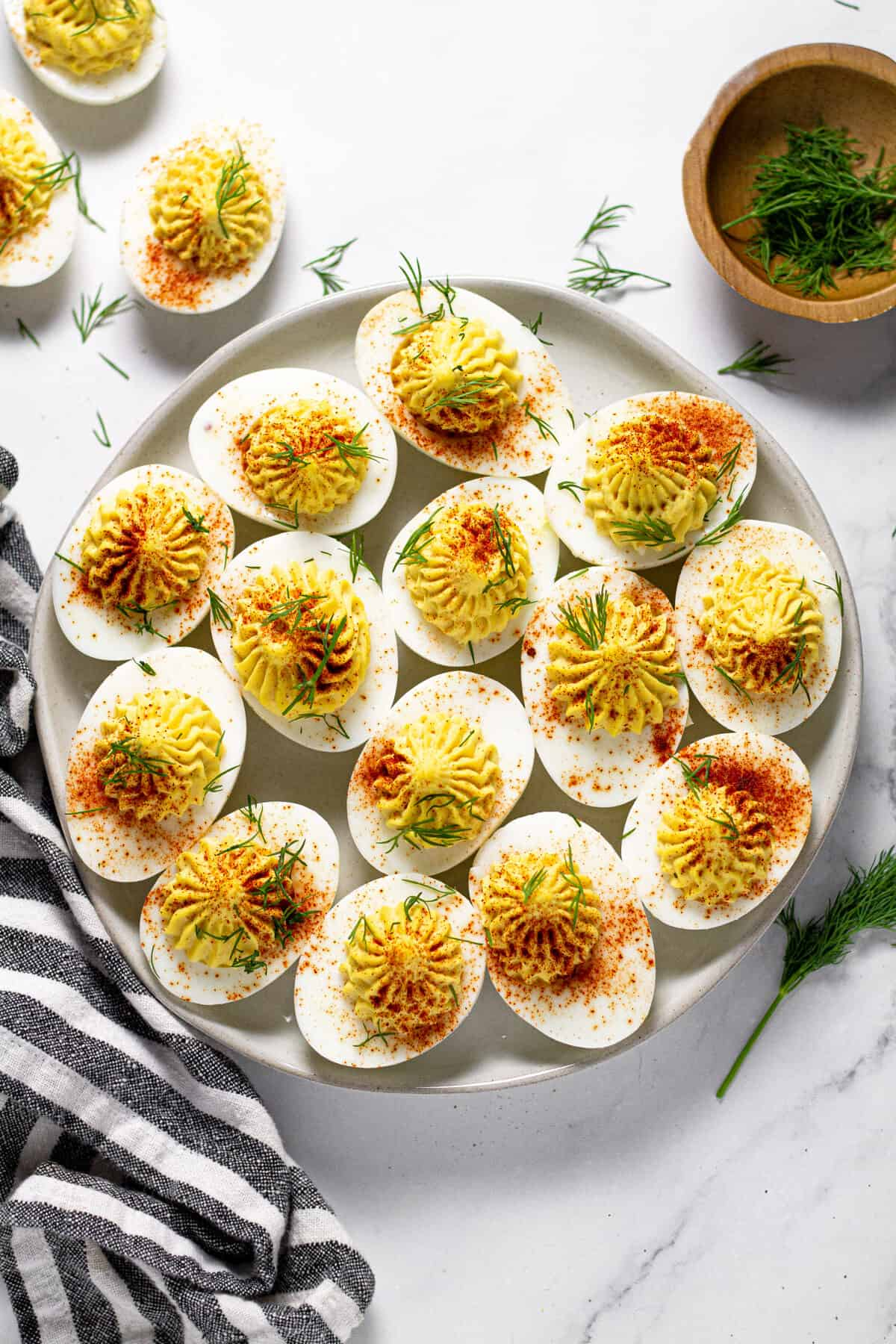 Overhead shot of a plate filled with deviled eggs on a white marble counter top