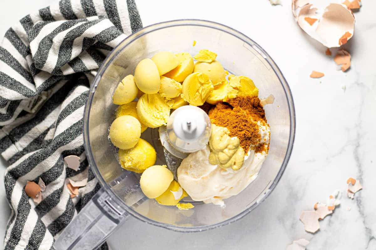Food processor with egg yolks and other ingredients to make deviled eggs