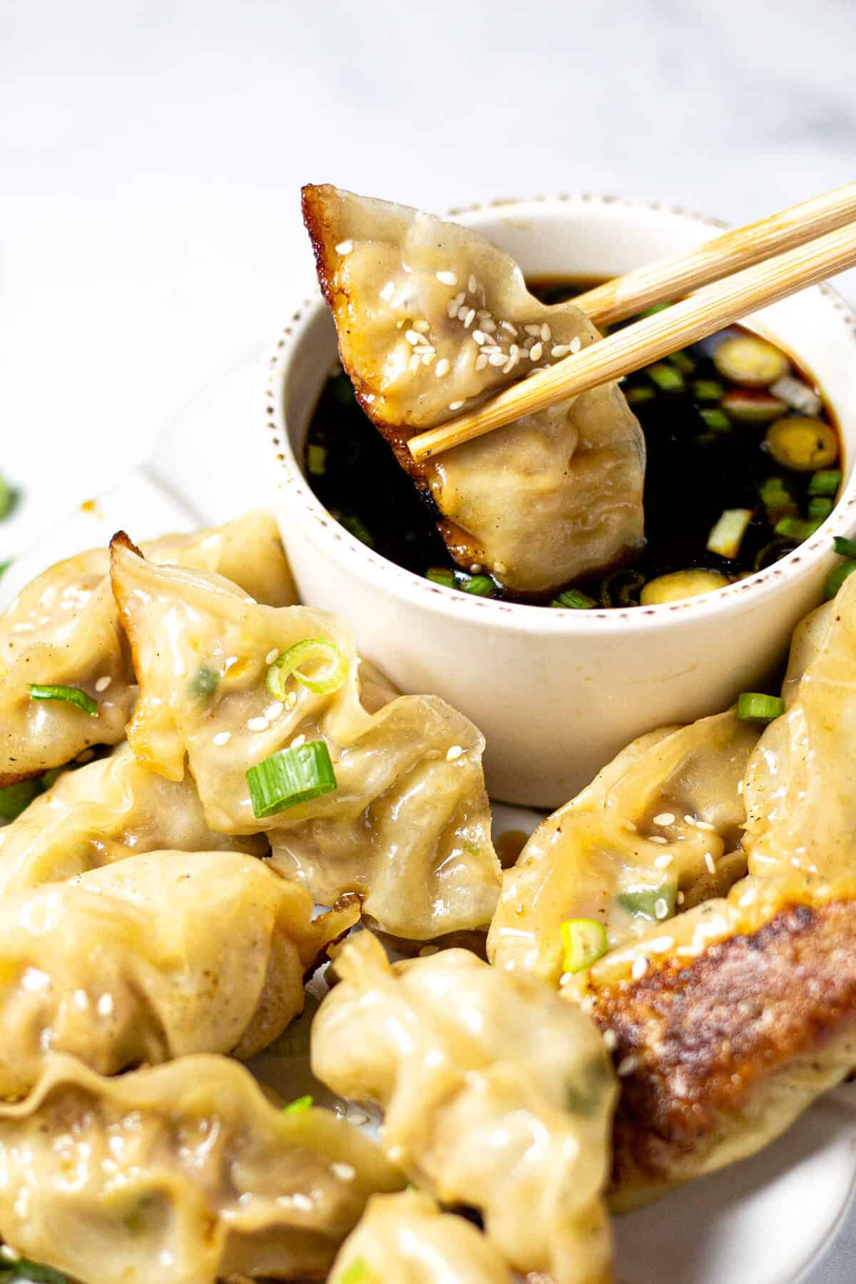 Close up shot of a pork dumpling being dipped in soy sauce with chopsticks