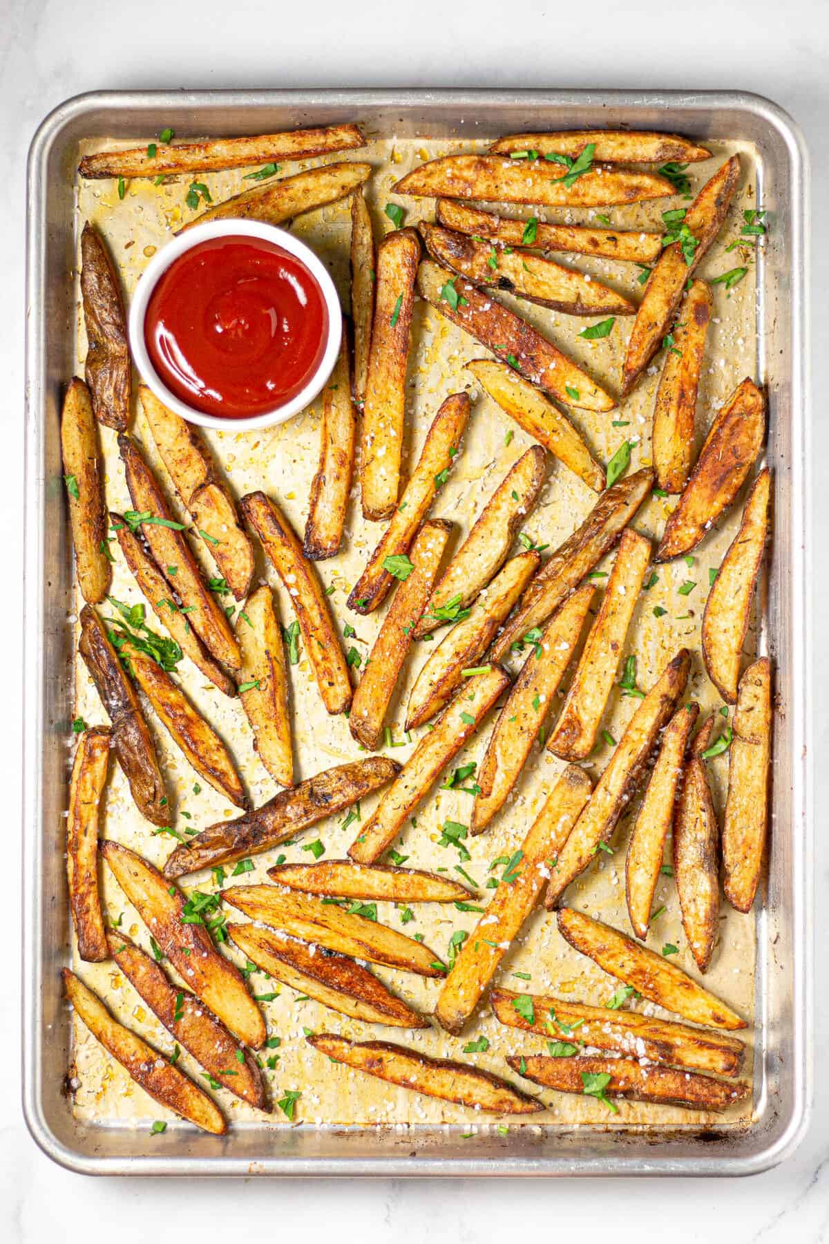 Overhead shot of a baking sheet filled with baked fries and ketchup